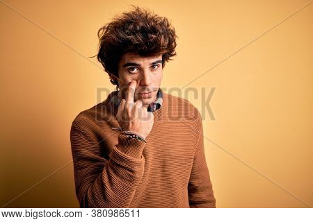 Young handsome man wearing casual shirt and sweater over isolated yellow background Pointing to the eye watching you gesture, suspicious expression