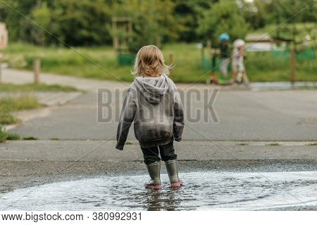 The Girl Is Playing In The Puddle In Rubber Boots