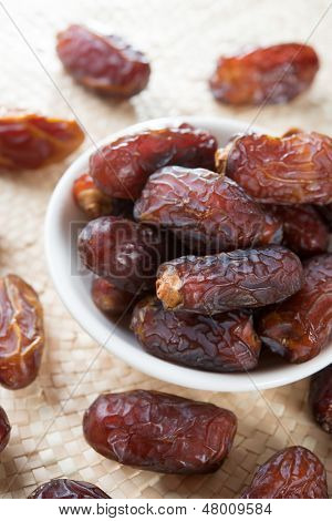 Dried date palm fruits or kurma, ramadan food which eaten in fasting month. Pile of fresh dried date fruits in a plate.