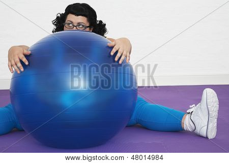 Tired overweight woman sitting behind exercise ball in healthclub