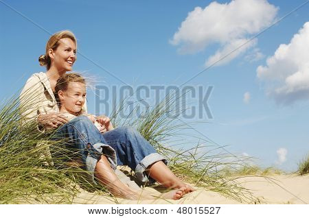 Happy mother and little daughter sitting on sand at beach