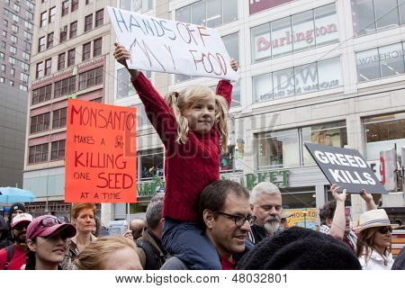 NEW YORK-MAY 25: At the March Against Monsanto an unidentified young girl holds a sign that reads 'Hands Off My Food' above the crowd in a global movement against GMO's on May 25, 2013 in Manhattan.