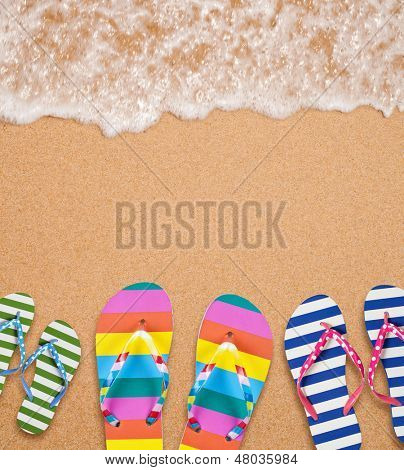 Family's flip flop pairs on sea surf with copy space for your text