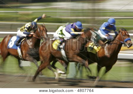 Slow shutter speed rendering of racing horses and jockeys poster