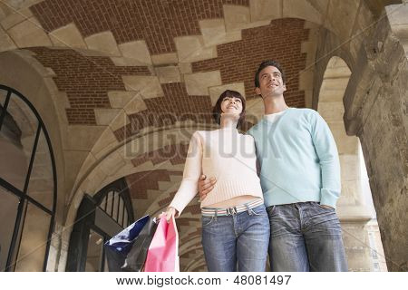 Low angle view of a young couple with shopping bags walking through archway