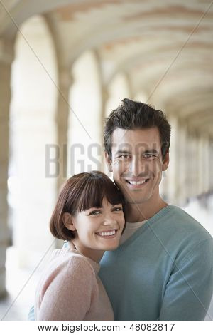 Closeup portrait of a smiling young couple embracing under archway