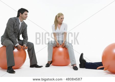 Young couple sitting on space hoppers and looking at fallen man against white background