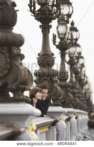 Side view of a young couple looking over bridge through streetlights