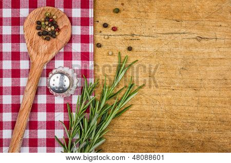 Rustic wooden background with checkered tablecloth and wooden spoon