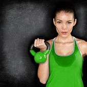 Fitness woman exercising holding kettlebell strength training biceps. Beautiful sweaty fitness instructor on blackoard background looking intense at camera. Asian Caucasian female model. poster