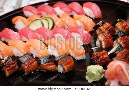rolls of various sushi on a plate poster