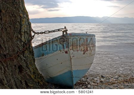 Rusty blue fishing boat tied on shore poster