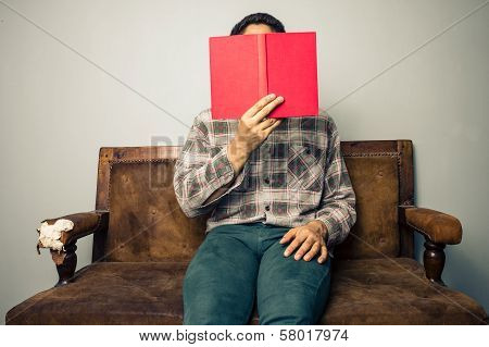 Man Hiding Behind Book On Old Sofa poster