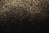Gold and silver glitter abstract background isolated on black poster