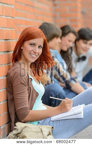 Student girl sitting in row outside campus friends in background