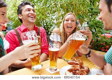 Friends drinking beer and having fun in beer garden in Bavaria