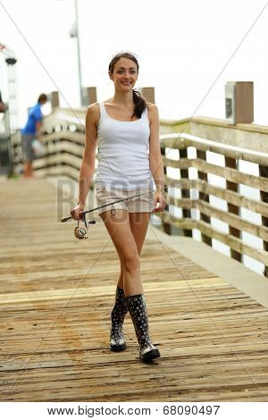 Woman walking with a fishing pole