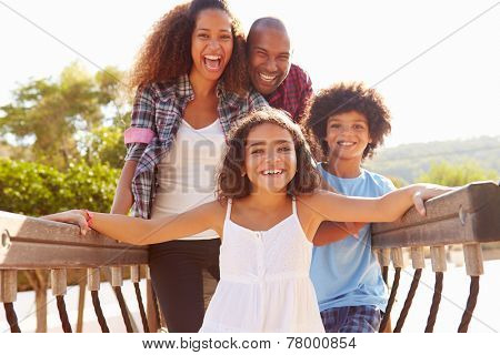 Portrait Of Family On Playground Climbing Frame