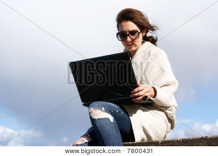 Young woman with laptop on beach