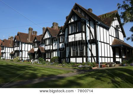 row of 19th century half timbered almshouses in tring hertfordshire poster
