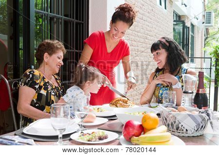 Beautiful hispanic family with senior woman and two daughters with a toddler enjoying lunch at the outdoor dining area in summer. Concept of togetherness and family bond.