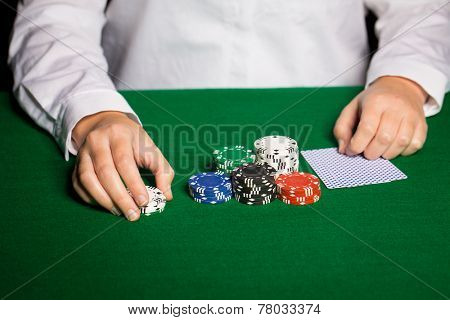 casino, gambling, poker, people and entertainment concept - close up of holdem dealer with playing cards and chips on green table poster