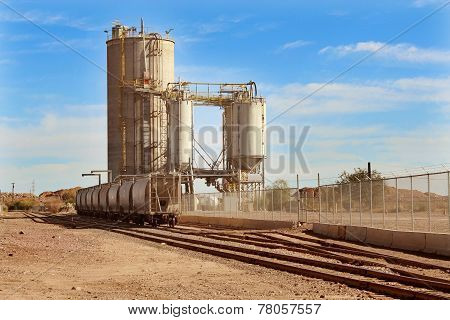 Stationary cargo train wagons next to Mill and Silo along train tracks in desert