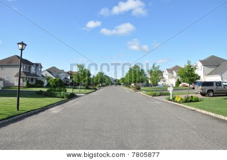 Empty suburban neighborhood community street on a clear spring day. poster