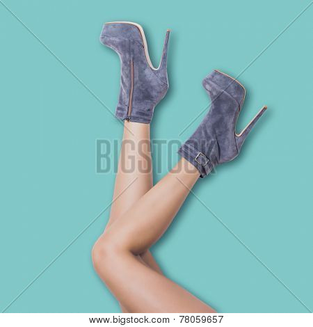 woman legs in velour high heel platform ankle boots lean on pastel blue wall upside down