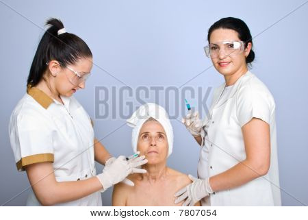 Doctor Inject To Senior Cheek Woman
