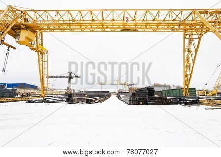 industrial scenery with bridge cranes and rolled metal products in warehouse poster