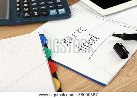 Message You're Fired on notebook on wooden table, closeup
