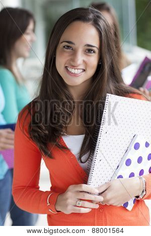 Smiling teenager with exercise books