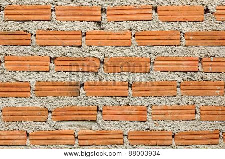Part of orange brick and cement wall