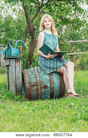 Portrait Of Barefoot Student Girl In Garden With Opened Book