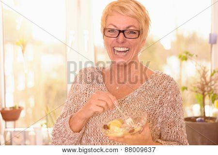 Vivacious Middle-aged Woman Eating Fruit Salad
