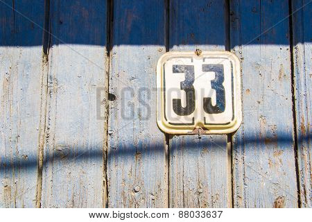 Number 33 On The Wooden Blue Chapped Wall
