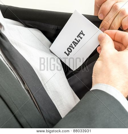 Businessman Showing A White Card Reading - Loyalty