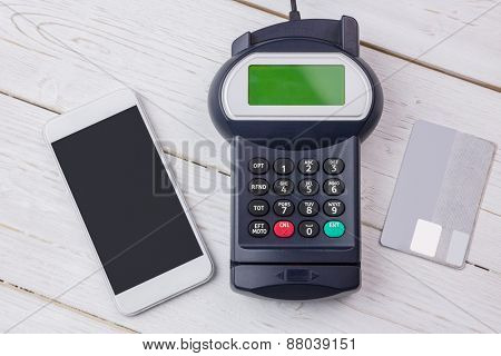 Overhead of pin terminal and smartphone on a wooden table