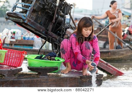CAN THO, VIETNAM, DECEMBER 12, 2014:A woman is washing the laundry on board of a commercial boat at the Cai Rang floating market on the Mekong river in Can Tho city, Vietnam.