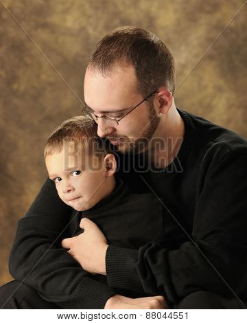 Close up image of a father snuggling with his young son who is grinning at the viewer from the corner of his eye.  Both are dressed in black.