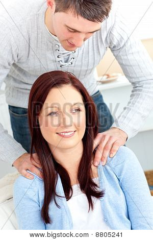 Concentrated Boyfriend Massaging His Cute Girlfriend's Shoulders In The Living-room