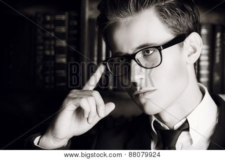 Close-up portrait of a respectable handsome man in his cabinet, library. Classic vintage style. Black-and-white photo.