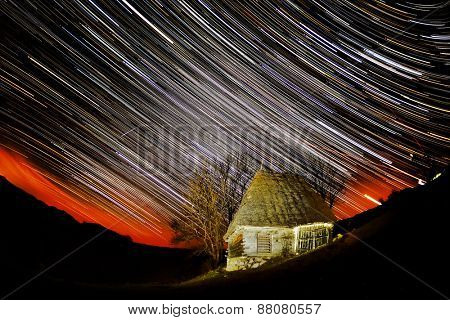 beautiful sky at night with startrails and silhouette of a rural house