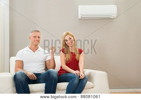 Young Happy Couple Sitting On Sofa Using Air Conditioner poster