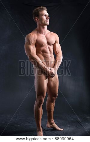 Totally naked male bodybuilder hiding genitalia with hands
