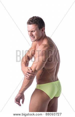 Muscular handsome man in underwear holding his elbow and arm, with one hand and grimacing in pain, isolated on white poster
