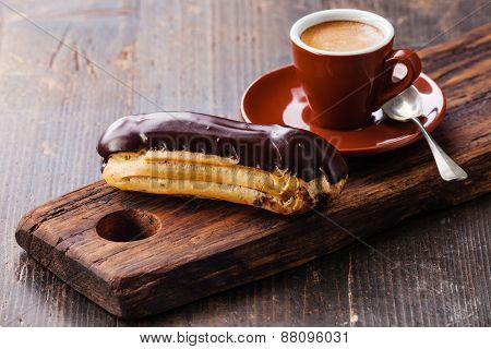 Chocolate Eclair And Coffee Cup On Dark Wooden Background