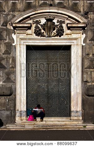 the brown gate in the church gesu nuovo in naples and a homeless reading a newspaper poster