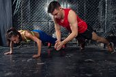 Sportsmen. fit male trainer man and woman doing clapping push-ups explosive strength training concept fitness workout strenght power. ** Note: Shallow depth of field poster